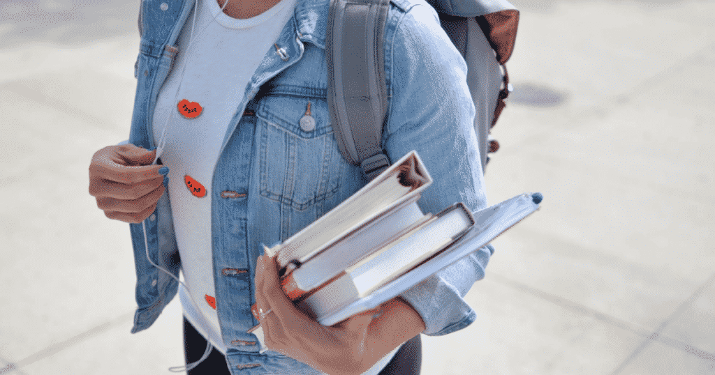 A student carrying books on her hands