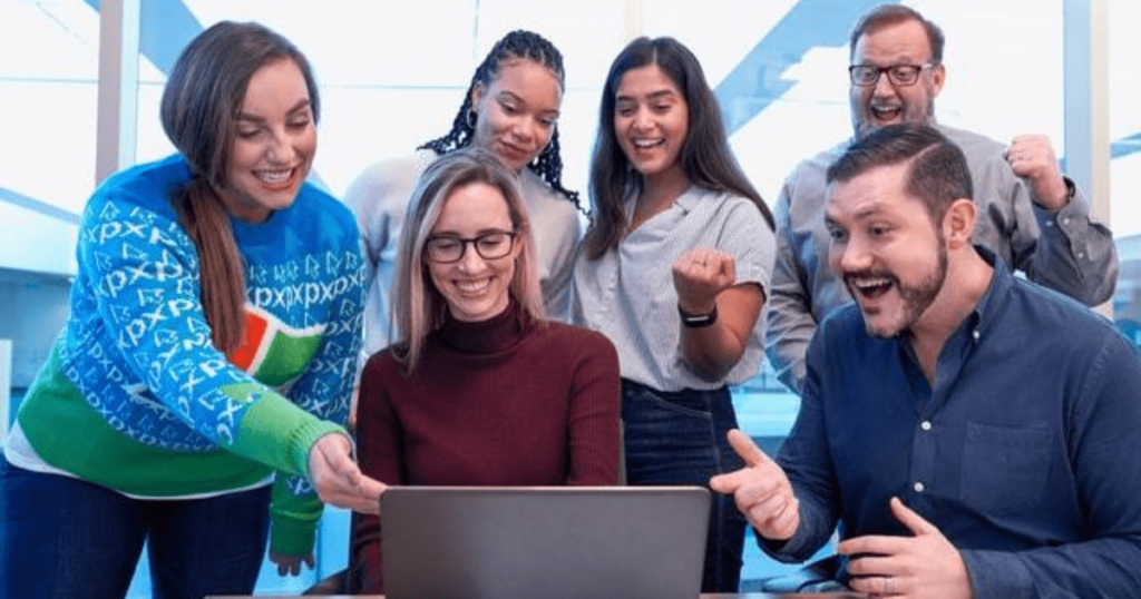 A group of students staring at something on a laptop