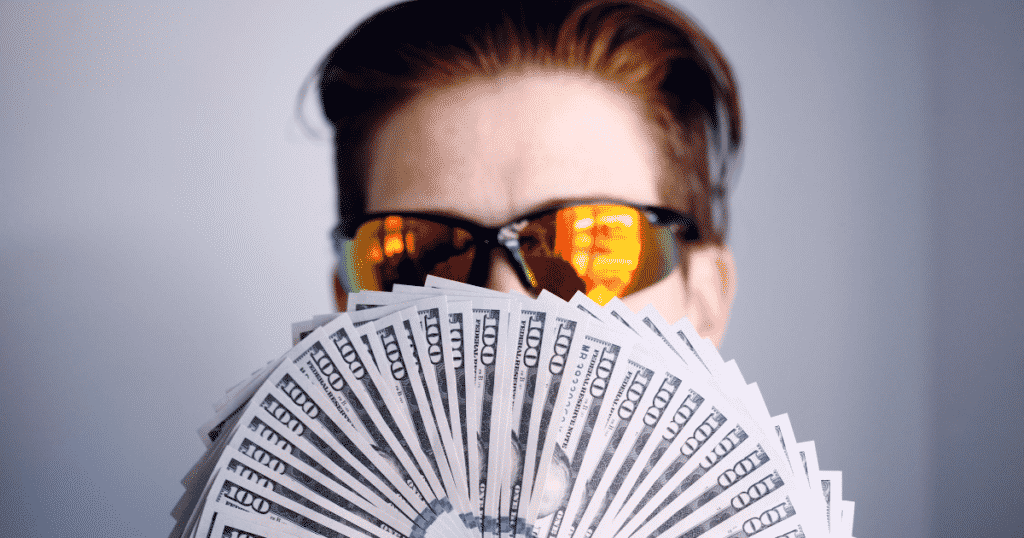 A person with sunglasses holding 100 dollar bills