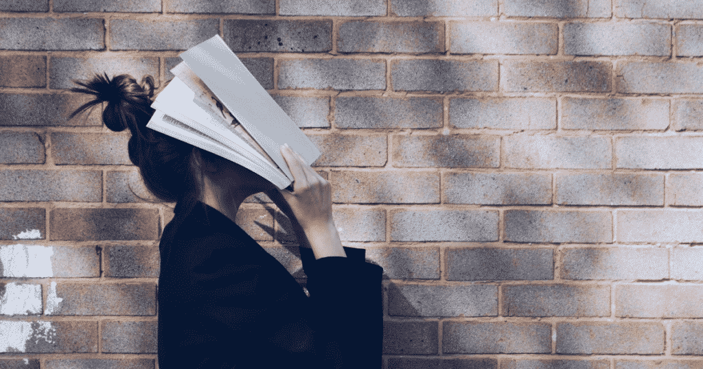 Aa woman covering her face with a book